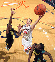 Dec. 17, 2010; Charlottesville, VA, USA; Virginia Cavaliers guard Sammy Zeglinski (13) goes to the basket between Oregon Ducks guard Jay-R Strowbridge (55) and Oregon Ducks guard Teondre Williams (22) during the game at the John Paul Jones Arena. Virginia won 63-48. Mandatory Credit: Andrew Shurtleff