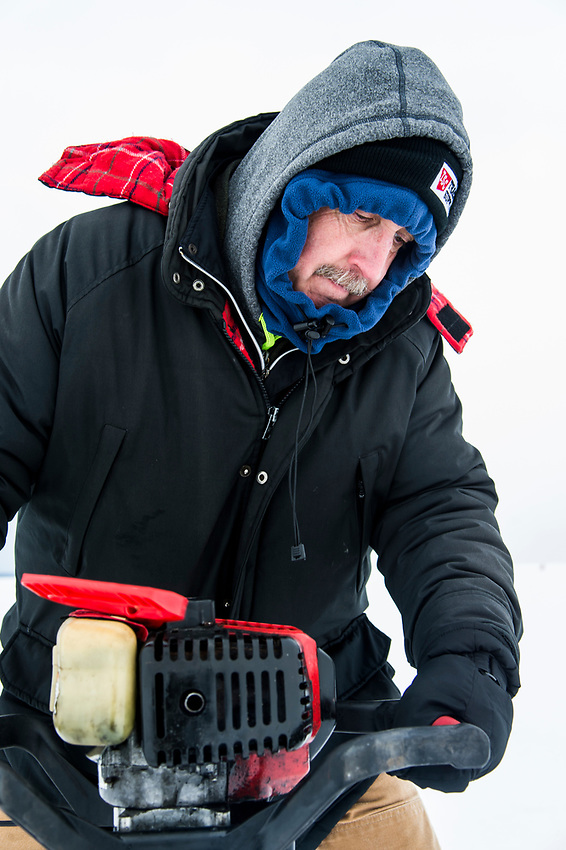 Writer Danny Lee drills ice fishing holes with an auger on Little Bay de Noc near Gladstone, Michigan.