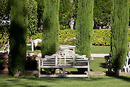 A decorative wooden bench sits along a line of cypress trees at a Chateau in Loriol-du-Comtat, France