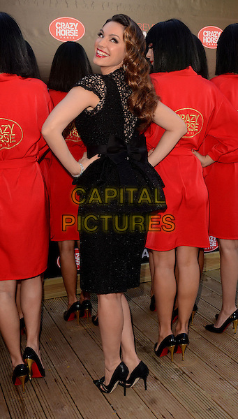 Kelly Brook .Photocall to annonce that she will be doing a one week stint in 'Forever Crazy' from the 1st November to the 8th November, Southbank, London, England..October 16th 2012  .full length black dress lace peplum bow hands on hips back behind rear looking over shoulder .CAP/WIZ.© Wizard/Capital Pictures.