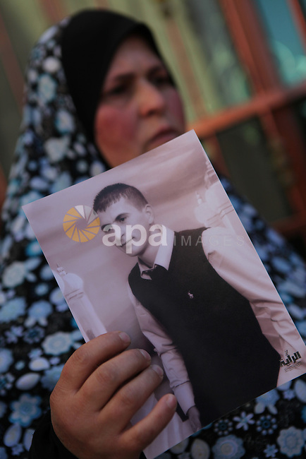 Mother of Hammam Hammam Masalma, the suspect in hit-and-run that left three soldiers injured, holds her son's picture, at her house in Beit Awwa, near the West Bank city of Hebron, November 6, 2014. The hit-and-run incident on the main Bethlehem-Hebron road on Wednesday night was the third such vehicular attack on Israeli soldiers and civilians in recent weeks, although the previous two took place in Jerusalem. Photo by Mamoun Wazwaz