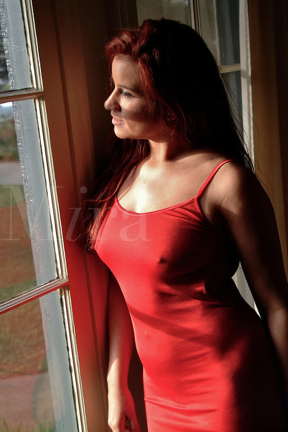 Side view of a young woman with red hair and in a red dress gazes out a window