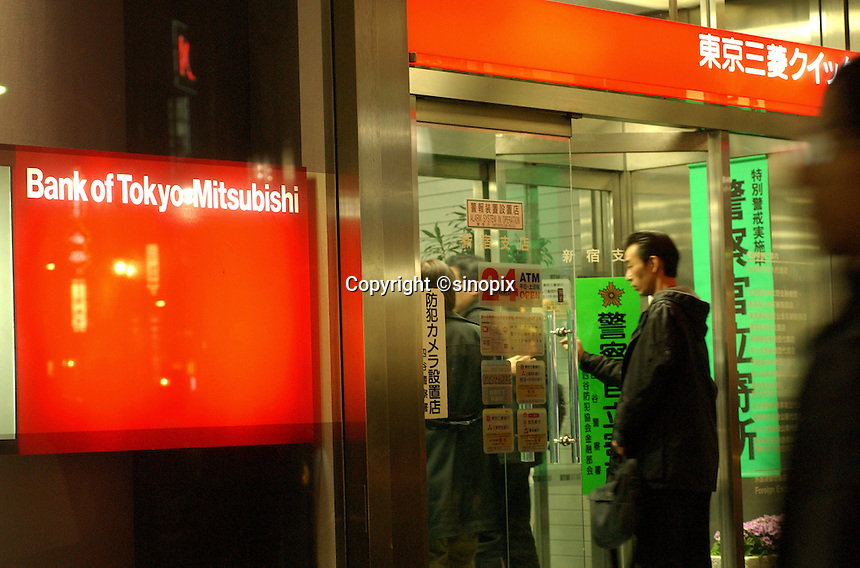 People at the entrance of the Bank of Tokyo-Mitsubishi in  Shinjuku district of Tokyo. Japan's banking system faces a crunch period in the months ahead due to the shrinking economy and biting recession....