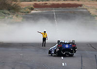Feb 22, 2014; Chandler, AZ, USA; Dust blows across the track as a Safety Safari member guides NHRA funny car driver Robert Hight around the turn off during qualifying for the Carquest Auto Parts Nationals at Wild Horse Pass Motorsports Park. Mandatory Credit: Mark J. Rebilas-USA TODAY Sports