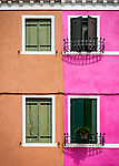 Orange and pink wall with windows in the colorful village of Burano, Italy.