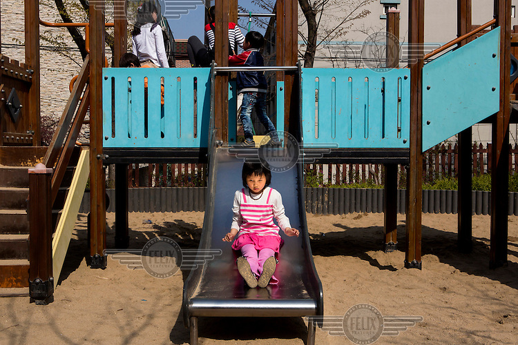 A child plays on a slide at the Kumgang School. It caters to children whose parents have defected from North Korea. /Felix Features