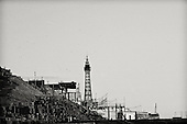 Herring Gulls circle over the man made landscape, and rocks forming part of the wall just above the main sea wall. Blackpool Tower sits along the promenade looking from North towards the South Beach and pleasure beach beyond.