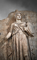 Close up of Roman Sebasteion relief sculpture personifing a Balkan Warrior  Aphrodisias Museum, Aphrodisias, Turkey.  Against a grey background.<br /> <br /> The relief figure personifies a Balkan Warrior tribe defeated by Tiberius in AD 6-8 before he became emperor. She wears a classical dress, cloak and helmet and carries a small shield and probably once a spear. A builder&rsquo;s inscription, &ldquo;Pirouston&rdquo;, written above the shield, ensured the relief was put on the right base