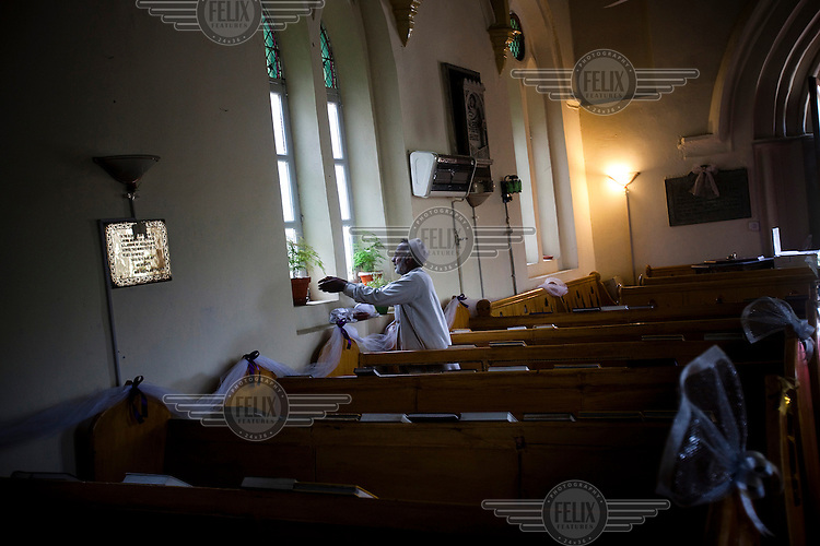A caretaker clears plants from the windows of St. Luke's Church following a wedding.