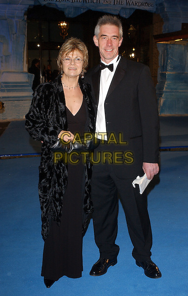 "JULIE WALTERS & GUEST.World Premiere of"" The Chronicles of Narnia: The Lion The Witch and The Wardrobe"" held at the Royal Albert Hall, London, UK..December 7th, 2005.Ref: BEL.full length black coat clutch purse tuxedo.www.capitalpictures.com.sales@capitalpictures.com.© Capital Pictures."