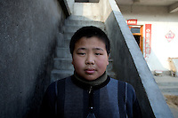 Fan Jian Bo, 11, was orphaned in 1998, and now lives with his aunt and uncle in Fanzhuang Village, Jiangsu Province, China.  The boy's father died of cancer in 1998, and soon after his mother committed suicide by drinking pesticide.  The boy's uncle has a cerebral embolism and the meager income the family earns from growing cabbages and melons cannot support Fan Jian Bo continuing school.  ..At the time of the picture, China's Amity Foundation charity, was investigating the family's situation in preparation to raise money to financially support these children and other orphans in similar situations.  With Amity's support, each orphan, aged 6-12, would receive approximately 1,400 RMB annually (about 200 USD) to pay for the cost of living. Amity works to keep children out of the institutional orphanages in China, preferring to provide monetary assistance that can help maintain a family environment for the orphans it helps.