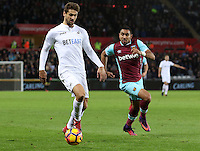 Gylifi Sigurdsson of Swansea City FC is closely marked by Dimitri Payet of West Ham United during the Premier League match between Swansea City and West Ham United at The Liberty Stadium, Swansea, Wales, UK. Monday 26 December 2016