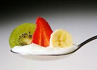 Still life di un cucchiaio con yogurt e frutta, kiwi, banana, fragola su sfondo bianco sfumato.<br /> Still life of a spoon with yogurt and fruit, kiwi, banana, strawberry on white gradient background.