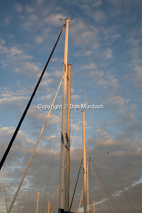 Sailboat masts against a cloudy blue sky