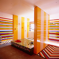 The Lego bedroom is a riot of colour with brightly striped walls in horizontal and vertical patterns and a zigzag patterned floor