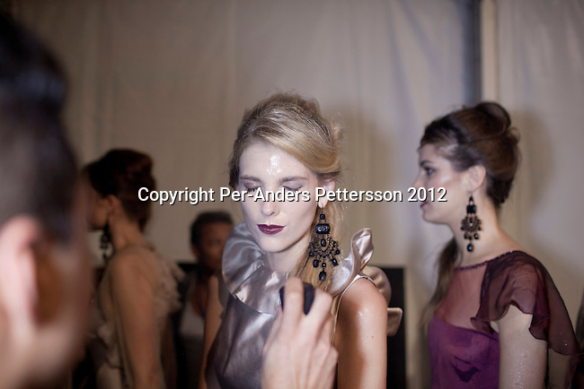 JOHANNESBURG, SOUTH AFRICA  MARCH 09: A model has been sprayed with water backstage before a show for the designers Kluk CGDT at the Joburg Fashion Week on March 09 2012, at the Hyde Park Mall in Johannesburg, South Africa. South Africa's finest designers showed their 2012 Autumn & Winter collections during the 4day event. (Photo by Per-Anders Pettersson)