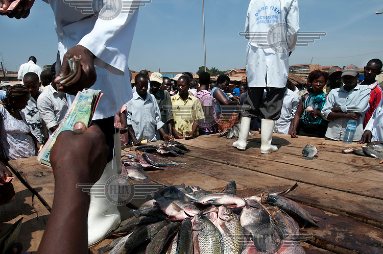 A woman offers money to a man selling fish caught in Lake Victoria.