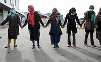 Pictured: Women hold hands in solidarity inside the camp Monday 06 February 2017<br /> Re: Scuffles between migrants and police broke out during a visit by Immigration Policy Minister Yiannis Mouzalas at the Elliniko migrant camp located in the former airport in the outskirts of Athens, Greece.