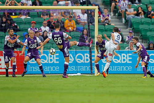 25th March 2018, nib Stadium, Perth, Australia; A League football, Perth Glory versus Melbourne Victory; Kosta Barbarouses of Melbourne Victory has a shot at goal during the first half as Dino Djulbic Shane Lowry Xavi Torres and Joseph Mills of the Perth Glory try to block the shot