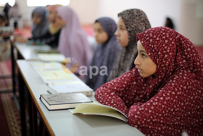 A Palestinian woman teaches young girls the Koran, Islam's holy book, at a religion school in Gaza City on June 21, 2016, during the Muslim fasting month of Ramadan. Photo by Mohammed Asad