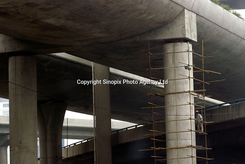 A construction worker work high in a scaffolding at a elevated highway construction site in Shanghai, China. .25 Oct 2005 .