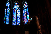 A visitor photographs a set of stained glass windows commissioned by Marc Chagall in 1971 in the cathedral of Notre-Dame de Reims, Reims, France, 11 November 2015