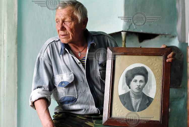 Vladimir Semonov, descendant of a White Army Lieutenant, has lived all his life in the village of Ust-Byur. He holds a picture of one of his ancestors who was an original settler in the village when white Russians were exiled in the early 1920s.