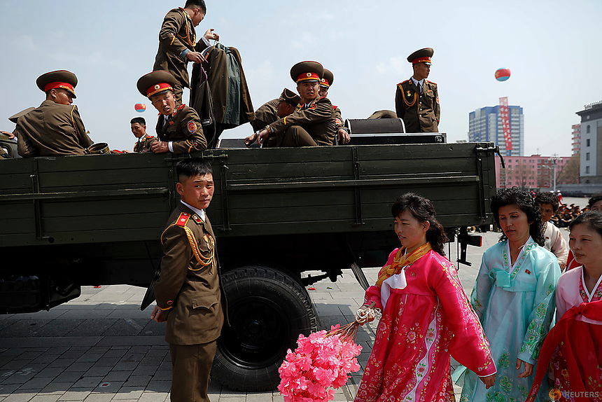 Women in traditional clothes walk past military band getting onto a truck after a military parade marking the 105th birth anniversary of North Korea's founding father, Kim Il Sung in Pyongyang, April 15, 2017.    REUTERS/Damir Sagolj