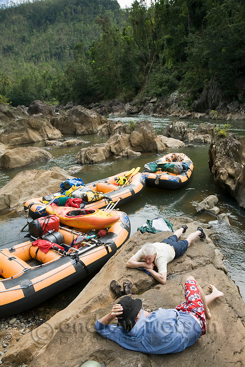 Rafters relaxing on riverbank during white water rafting expedition on North Johnstone River.  Wooroonoonan National Park, Queensland, Australia