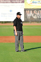 Umpire Ryan Powers handles the calls on the bases in the Pioneer League League game between the Ogden Raptors and the Idaho Falls Chukars at Lindquist Field on July 26, 2014 in Ogden, Utah.  (Stephen Smith/Four Seam Images)