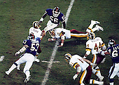 New York Giants linebackers Lawrence Taylor (56) and Harry Carson (53) close in for a sack on Washington Redskins quarterback Joe Theismann (7) at RFK Stadium in Washington, D.C. on Monday, November 18, 1985. Theismann suffered a career-ending injury on the play.  The Redskins won the game 23 - 21..Credit: Arnie Sachs / CNP