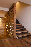 The stairwell is clad in large planks of old timber to match the floorboards
