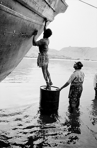 Sur, Oman<br /> July 2001<br /> <br /> Dhow boat builders also clean the underbelly of older wooden ships.