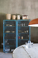 An old blue French metal parachute locker is used as a kitchen cupboard to store tableware and glassware.