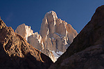 Fitz Roy is bathed in light behind some shadowed ridges.