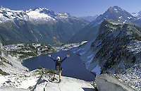 Hiker above Hidden Lake with arms stretched out, Hidden Lake Trail, North Cascades National Park, Cascade Mountains, Washington