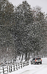 18 January 2008: A vehicle travels a country road over fresh snow, lined with a wood fence, trees and the landscape at Shelburne Farms, in Shelburne, Vermont, USA...Mandatory Photo Credit: Ed Wolfstein Photo