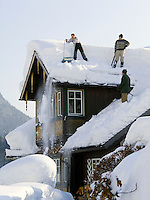 Austria, Styria, Styrian Salzkammergut, Altausseerland, Altaussee at Altausseer Lake: men shovelling snow from the roof