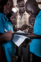 Teacher THAMAS MAKAY passes out graded papers and answers students questions at an emergency school in the UN Protection of Civilians camp for internally displaced people in Juba, South Sudan. More than 24,000 people live in the POC on the United Nations compound.