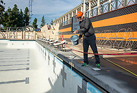 Tom Polansky, Associate VP of Facilities, pours a bucket of water from Taylor Pool into the new pool of the De Mandel Aquatic Center at Occidental College, Dec. 12, 2019.<br /> (Photo by Marc Campos, Occidental College Photographer)