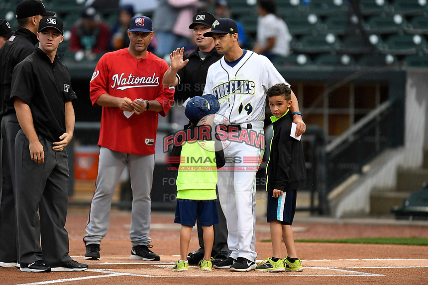 South All-Stars manager Jose Leger (19) of the Columbia Fireflies meets with the umpires with his two sons at the beginning of the South Atlantic League All-Star Game on Tuesday, June 20, 2017, at Spirit Communications Park in Columbia, South Carolina. With him is North manager Patrick Anderson of the Hagerstown Suns. The game was suspended due to rain after seven innings tied, 3-3. (Tom Priddy/Four Seam Images)