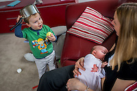 A woman sitting on a sofa breastfeeding her 2 month old baby daughter while interacting with one of her older sons who is playing with a saucepan.<br /> <br /> Hampshire, England, UK<br /> 10/02/2013