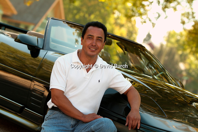 Hispanic man in front of his car