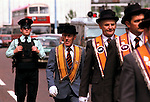 Armed policeman walks behind an Orange Day Parade, Belfast Northern Ireland 1980s. UK