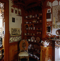 A china tea service displayed on fretwork shelving in the corner of the room