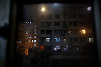 "An apartment block is seen through the window of a space where people live in wooden boxes early October 9, 2012 in Hong Kong. In Hong Kong's middle-class residential area, short distance from its shopping and financial districts, 24 people live in ""coffin homes"" packed in a single apartment of little over 50 square meters. Its residents pay monthly 1450 Hong Kong dollars (around 180 USD) for their living space built of wooden panels of 2 meters by 70 cm. To maximize income from the rent in central Hong Kong, landlords build such coffin homes, nicknamed because of their resemblance to real coffins. Space has always been at a premium in Hong Kong where developers plant high-rises on every available inch.   REUTERS/Damir Sagolj (CHINA)"