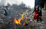 People stay warm around a trash fire in a Roma settlement under a highway bridge in Belgrade, Serbia, in February 2012. The families that lived here, most of whom survive from recycling cardboard and other materials, were forcibly evicted in April 2012. Many were moved into metal shipping containers on the edge of Belgrade..