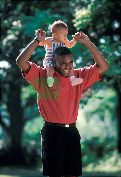 father carrying young toddler boy on his shoulders