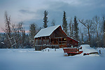 Montana, western, Flathead Valley, Kalispell. An old  barn and vintage truck in a snowy landscape at dawn.