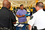 Arlando Van Hook of Florissant (center) speaks with representatives of the Clayton police department, Patrolman Derek Walker (left) and Lt. Al Thuet at a Diversity Fair sponsored by the St. Louis County branch of the Ethical Society of Police. The fair was held at Hazelwood Central High School on Saturday August 11, 2018 with police agencies from ten different jurisdictions represented.   Photo by Tim Vizer